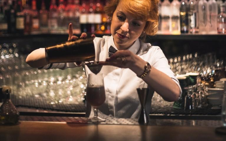 barmaid o barlady prepara un cocktail